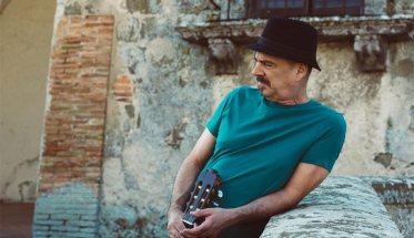 Il compositore Lo Martill appoggiato ad un parapetto con la chitarra, una maglietta verde e il cappello nero in testa