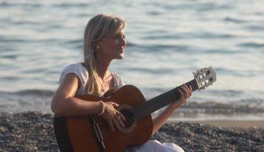 Mirael in riva al mare con la chitarra
