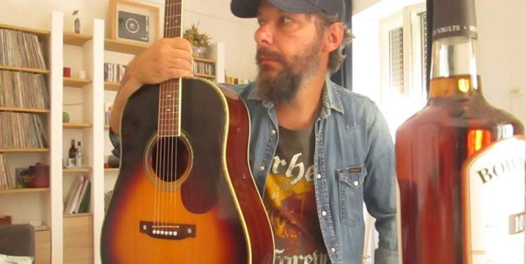 Daniele Marini con la chitarra in mano e un cappellino in testa
