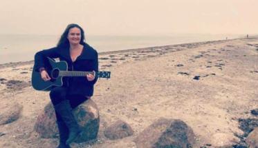La cantautrice Barbara Borgelin sulla spiaggia mentre suona la chitarra