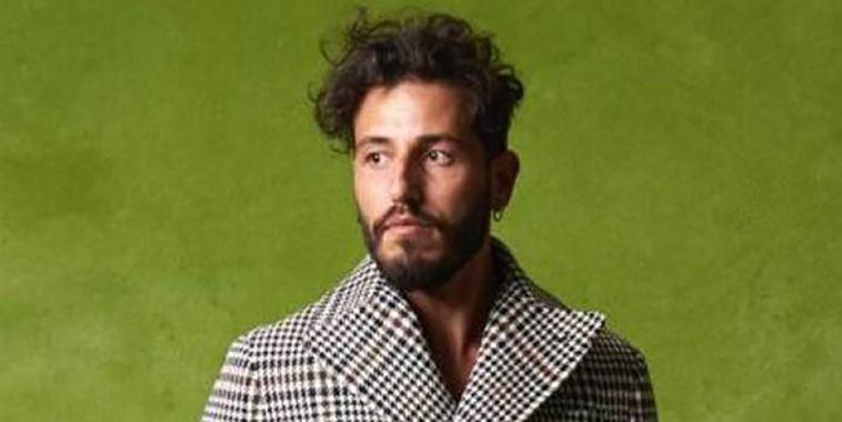 Il cantautore Limbrunire davanti ad uno sfondo verde acido