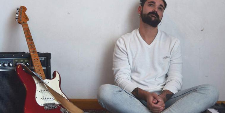 Il cantautore Martiny seduto per terra con vicino la sua chitarra, un amplificatore e una tastiera