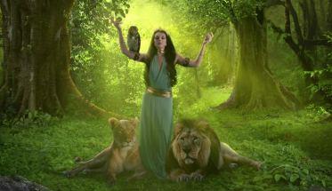 La cantautrice e danzatrice Inanna in una foresta con due leoni