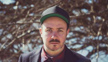 Il cantautore Al The Coordinator con un cappellino verde in testa