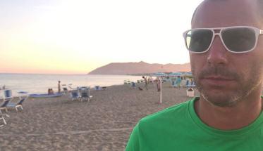 Aleco sulla spiaggia con magliette verde e occhiali da sole