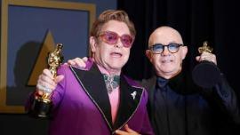 Elton John con in man o la statuetta e Bernie Taupin alla cerimonia degli Oscar 2020