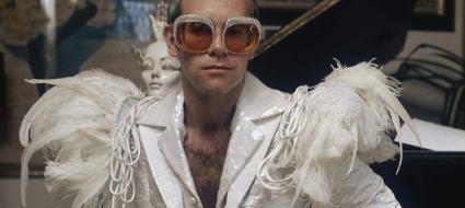 Elton John vestito di bianco con delle piume sulle spalle