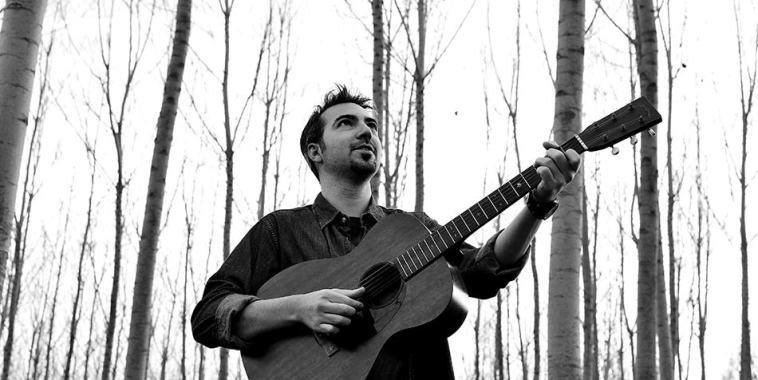 Lorenz Zadro con chitarra in un bosco