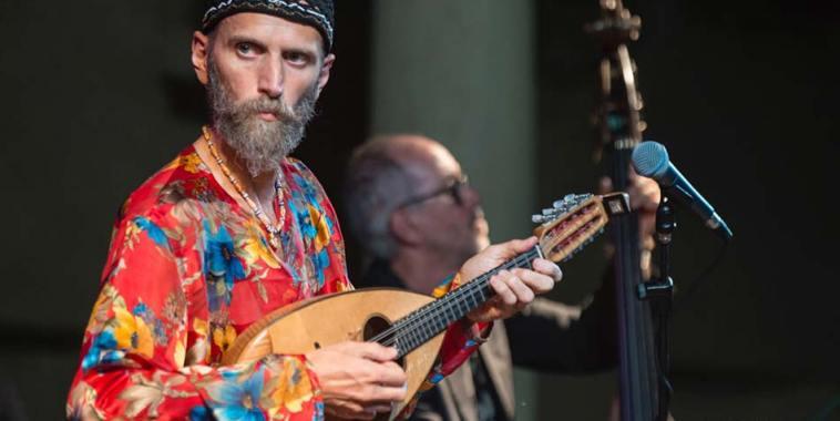 Carlo Aonzo con camicia rossa a fiori mentre suona il mandolino
