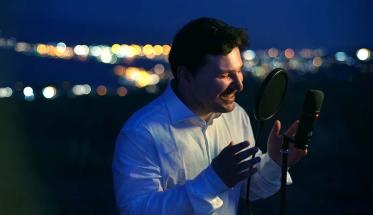 Il cantautore Nevì all'aperto di notte, con microfono e luci della città sullo sfondo