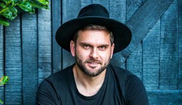 Danilo Sapienza con cappello seduto davanti da una porta di legno
