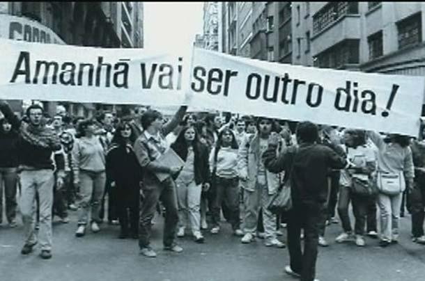 """Corteo di giovani manifestanti con in testa le parole di """"Apesar de você"""""""