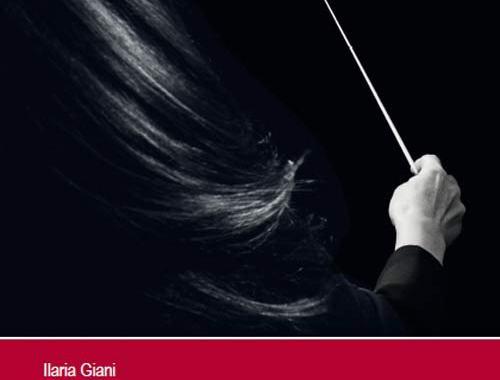 una donna di spalle che dirige con bacchetta da orchestra in mano