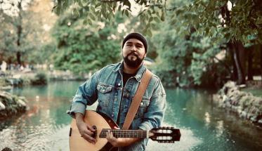Ludwig Mirak con la chitarra davanti ad un laghetto