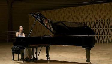 Cristina Cavalli mentre suona un pianoforte a coda