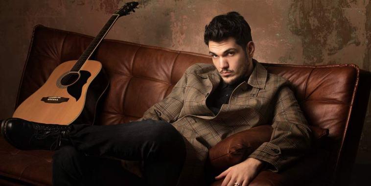Luca Gaudiano seduto su un divano con la chitarra
