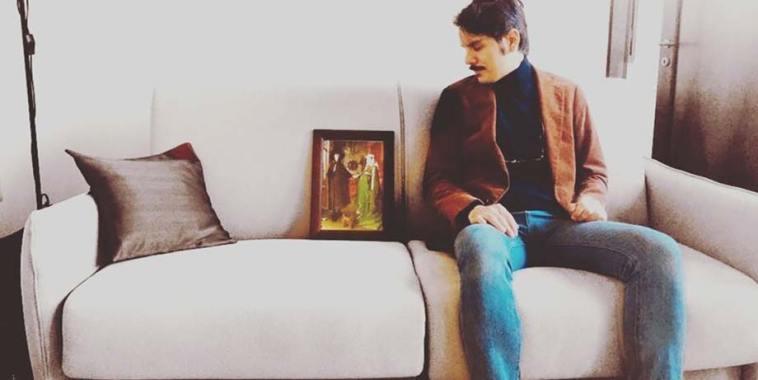Romano, il cantautore è seduto sul divano e guarda un ritratto