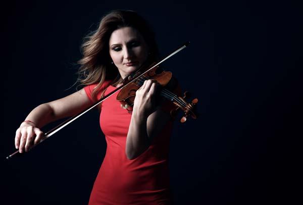 Anca Vasile Caraman vestita di rosso mentre suona il violino