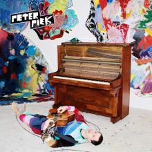Peter Piek sdraiato per terra con la chitarra vicino ad un pianoforte in copertina del disco Walking Zschopau