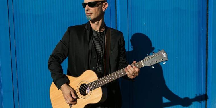 FINAZ con la chitarra acustica e un fondo blu alle spalle