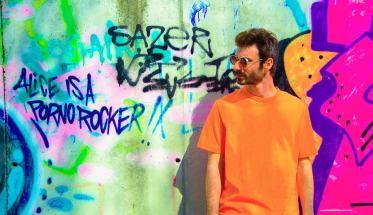 Il cantautore Limoni davanti ad un muro con graffiti