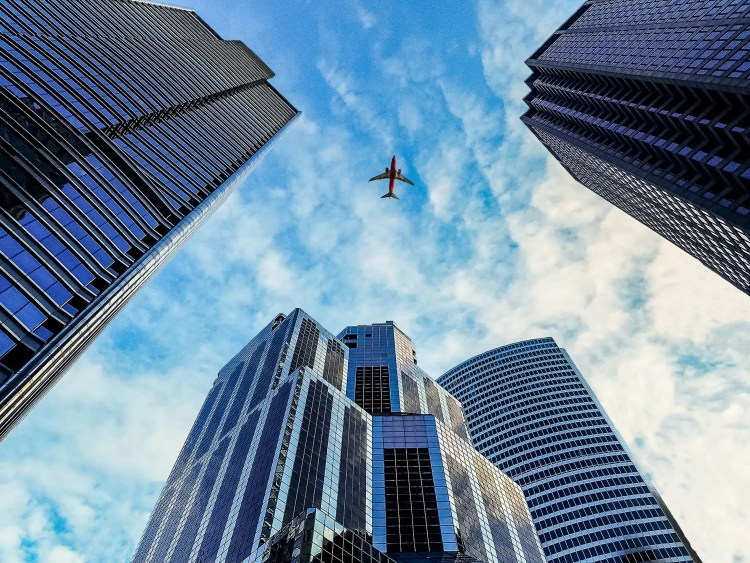 worm's eye view of airplane passing by buildings