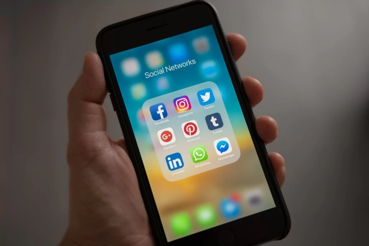 person holding iphone showing social networks folder