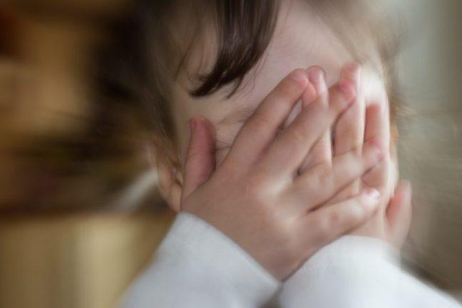 Criança com o rosto coberto pelas mãos