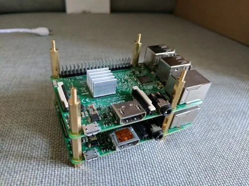 A Raspberry Pi 3 sitting atop a Pi 2 on cloth