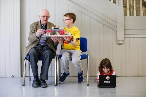 a boy showing a technology project to an old man, with a girl playing on a laptop on the floor — Coolest Projects North America