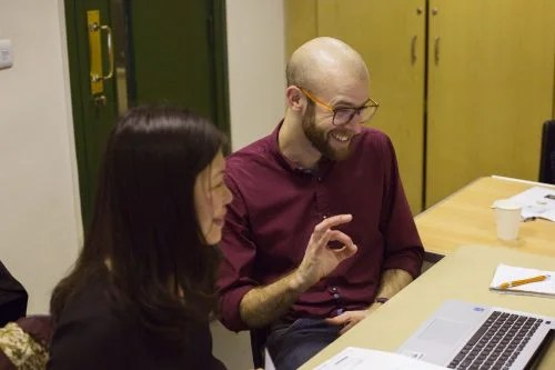 "A woman and a man sit at a desk, evidently collaborating on work on a laptop. The woman is smiling and the man is grinning and making an ""A-OK"" hand gesture."