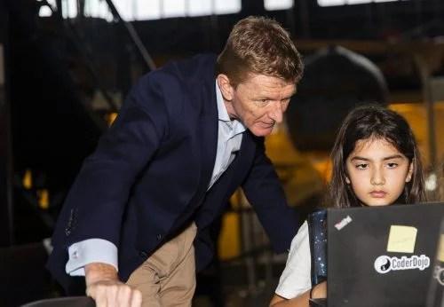 Tim Peake observes a girl writing code that will run in space