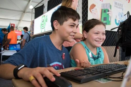 A smiling boy and girl looking at a computer screen