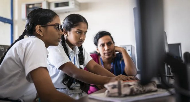 Two girls coding at a computer under supervision of a female teacher
