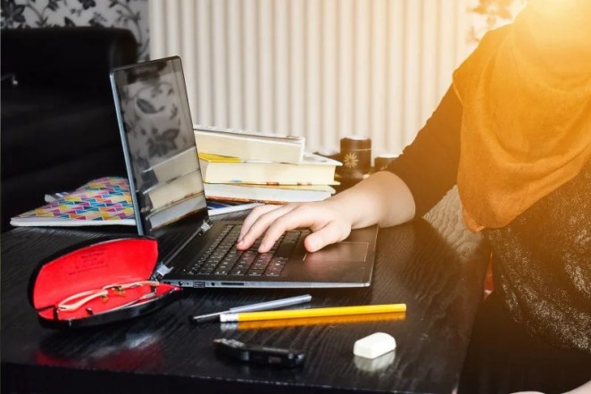 A girl in a hijab learning at home at a laptop