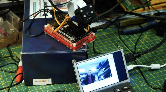 face recognition software running on small screen with raspberry pi camera behind it, looking at the maker