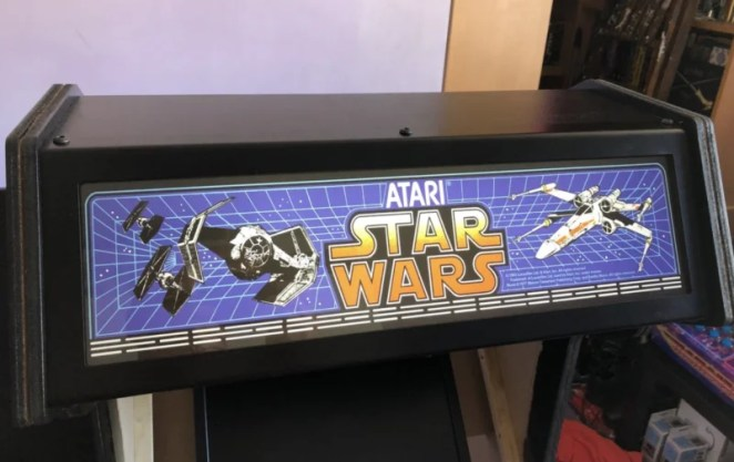 header of the arcade cabinet bearing a Star Wars logo