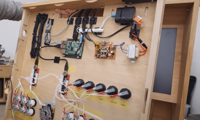 Back end of the arcade structure with raspberry pi and speakers and wires for buttons