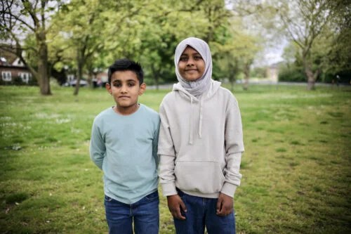 A girl and boy standing on the grass in a park