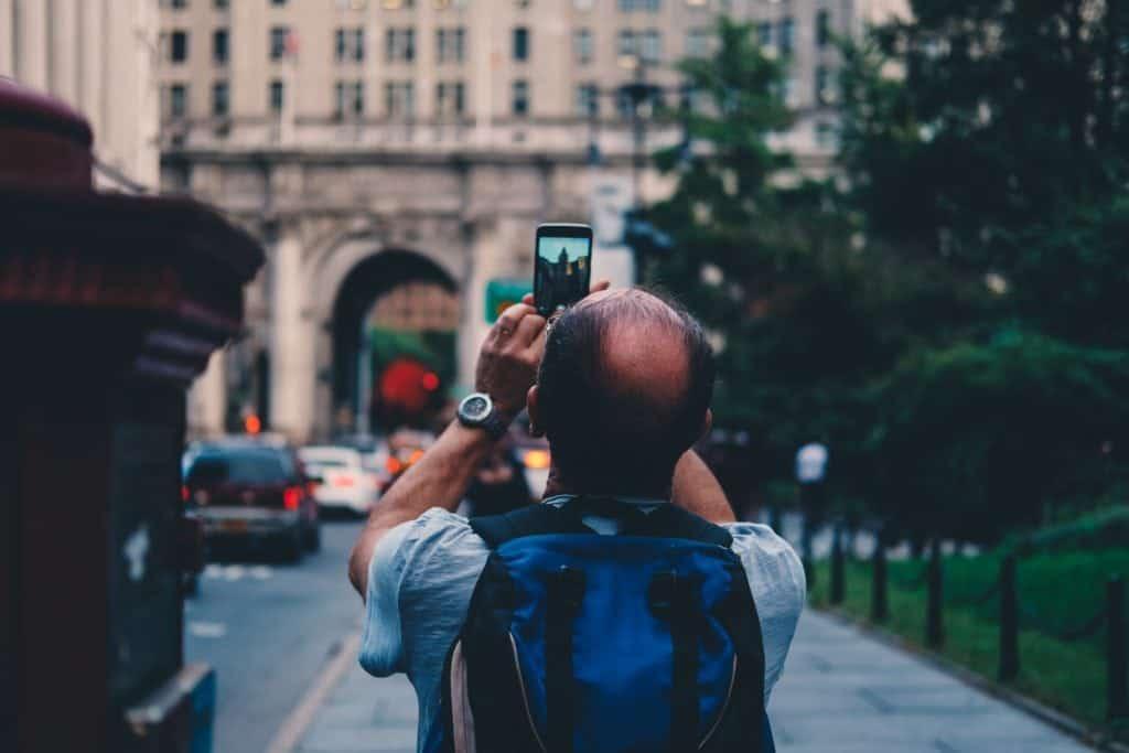 Baby boomer tourist taking photo on phone