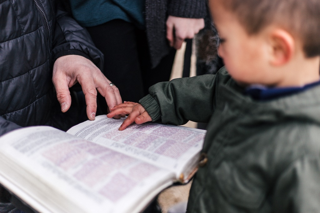 Child pointing at a bible