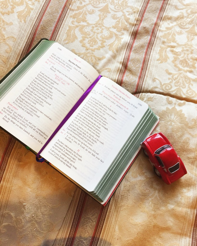 liturgy of the hours ordinary time book with red car on the bed