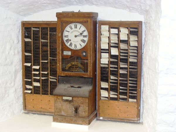 Wooden time clock, clock in centre with time cards either side