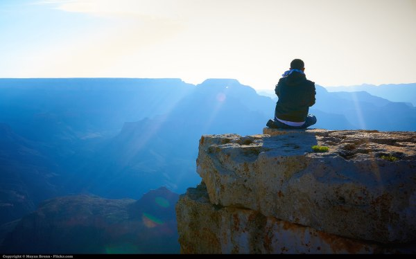 A man sitting with his back to us, watching the sun rise over the Grand Canyon