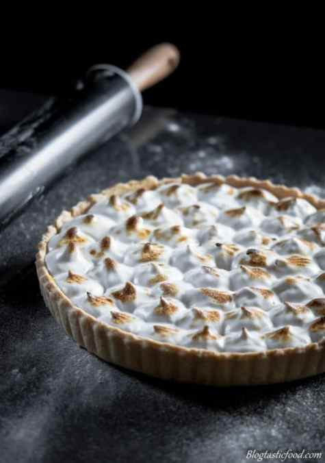 A photo of a vegan lemon meringue pie with flour dusted round it.