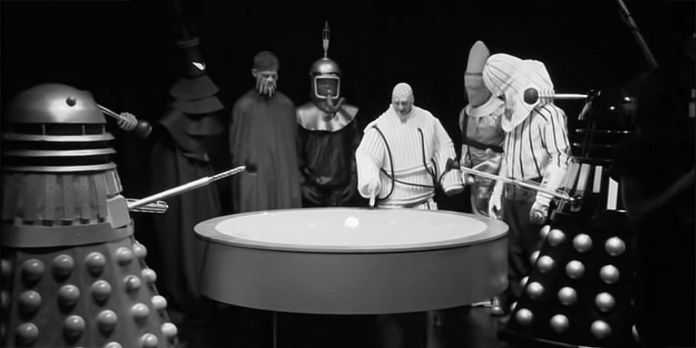 Paul Stenton as Malpha (in white) leads the alien delegates (Adam Ian Barry Traill, Benjamin Clarke, Edward Kelly, Gary Tatham, Joseph Burke) into alliance with the Daleks in Mission to the Unknown (c) BBC Studios/UCLan