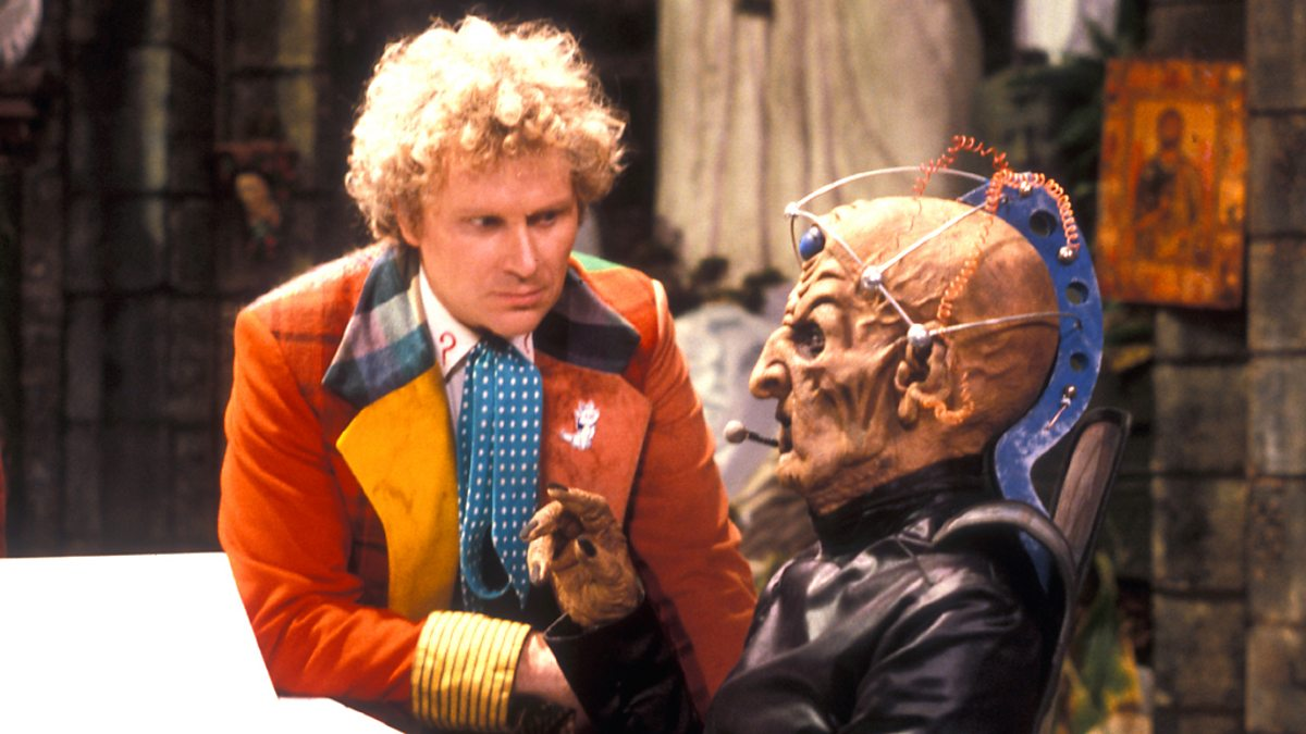 The Sixth Doctor (Colin Baker) and Davros (Terry Molloy) in Revelation of the Daleks (c) BBC Studios Doctor Who Sixth Doctor