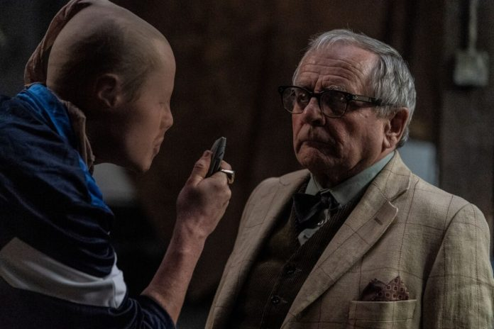 Nathan (Ian Kenny) threatens Dr. Huggins (Sylvester McCoy) to gain access to his safe (c) Blue Light/Logical Pictures/Wild Bunch Doctor Who Seventh Doctor The Owners