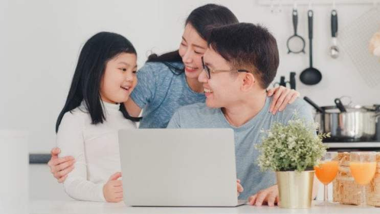Parents using laptop with daughter