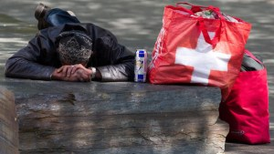 A homeless man sleeping on a bench next to his bas with a Swiss flag, in Geneva, Switzerland, Sunday, April 17, 2011. (KEYSTONE/Salvatore Di Nolfi)